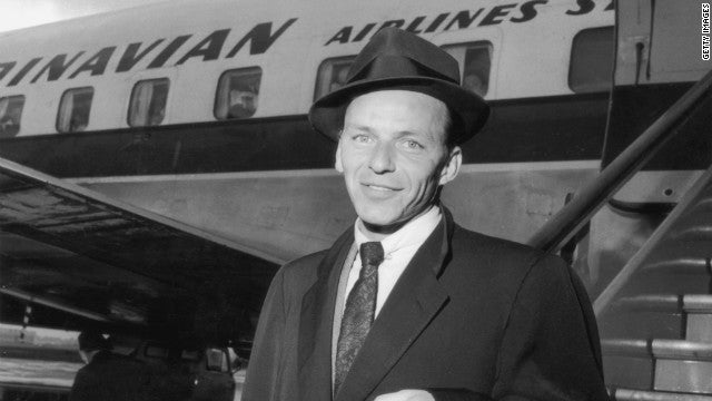 Frank Sinatra on the tarmac wearing a fedora
